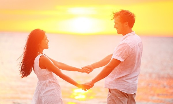 Romantic couple lovers holding hands at beach sunset. Happy mult