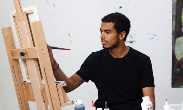 Young man painting on canvas --- Image by © Ann Summa/Corbis