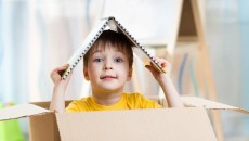 kid boy playing in a toy house in children room